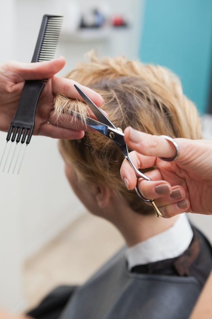 Hairdresser cutting acustomers hair at the hairdressers