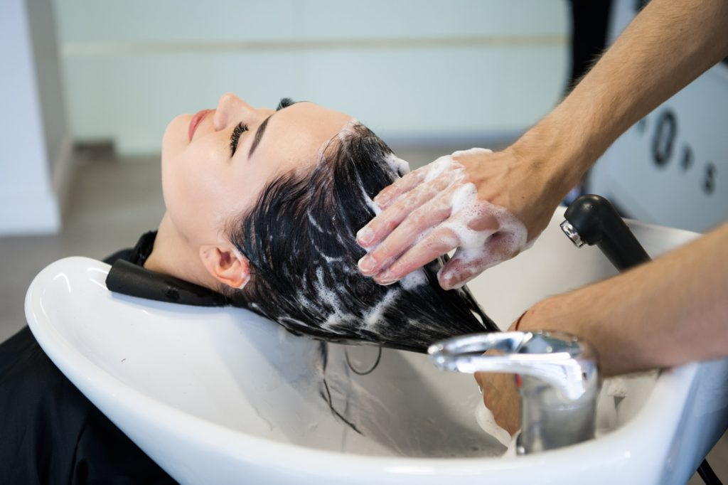 Unrecognizable professional hairdresser washing hair to her client. Beautiful hairdresser washing