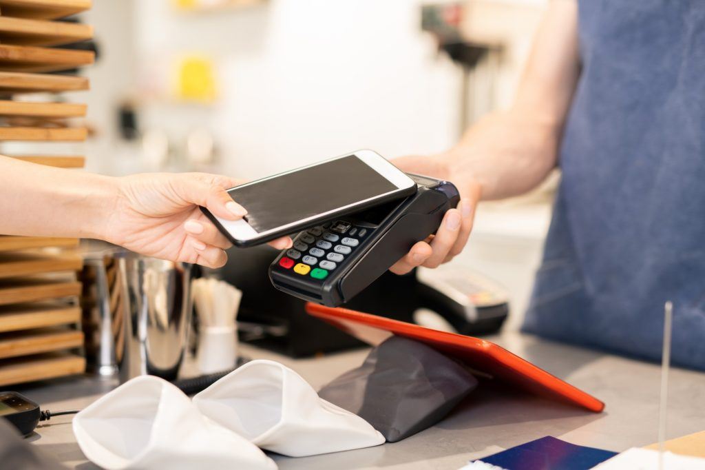 Hand of young woman holding smartphone close to electronic payment machine
